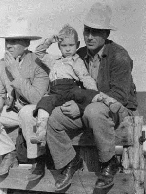 Texan and son sitting on fence at horse auction, Eldorado, Tx 1939
